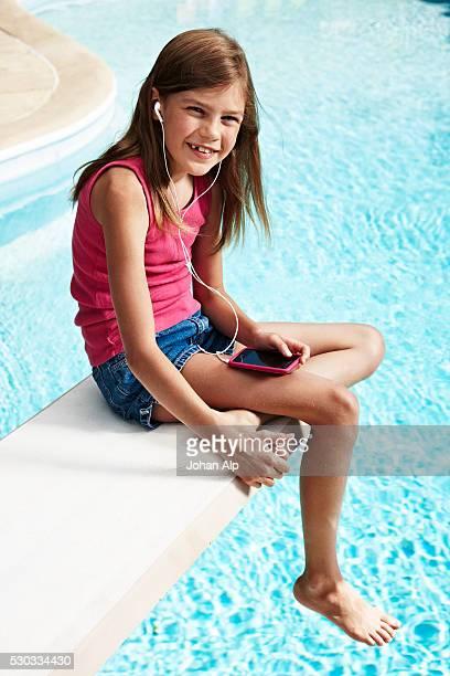 portrait of girl with mp3 player at swimming pool - 6 7 jaar stockfoto's en -beelden