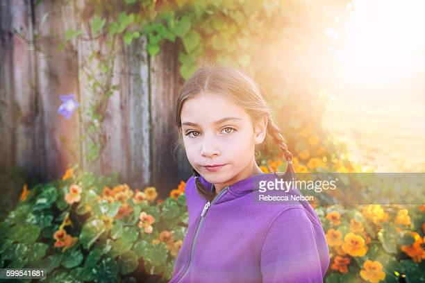portrait of girl with plaits in front of orange flowers looking at camera - rebecca nelson stock pictures, royalty-free photos & images