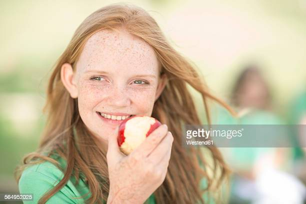 Portrait of girl with red hair eating an apple