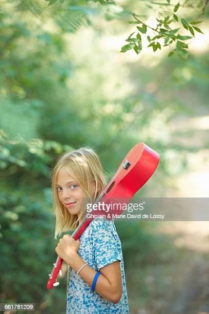 Portrait of girl with red ukulele in woodland, Buonconvento, Tuscany, Italy