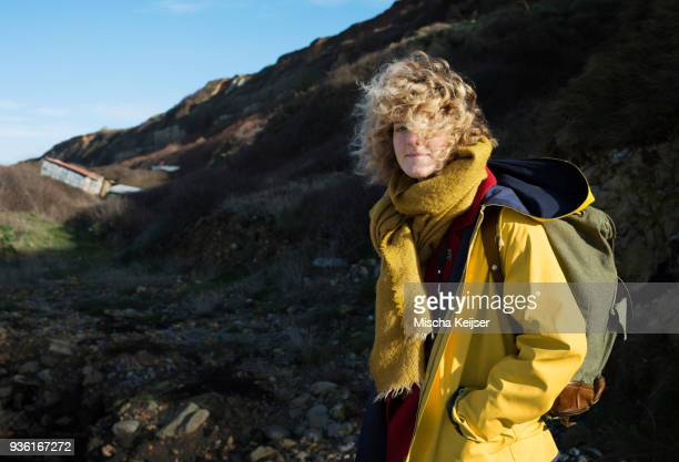 Portrait of girl with retro backpack hiking near former NATO fuel station on Normandy coast