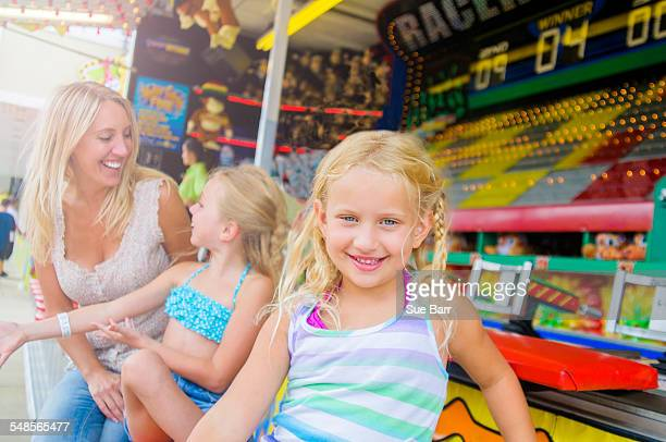 Portrait of girl with sister and mother in front of fairground stall