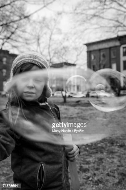 portrait of girl with soap bubble outdoors - marty hardin stock photos and pictures