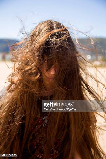 Portrait Of Girl With Tousled Hair While Standing At Beach