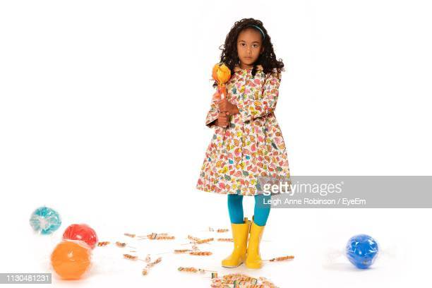 Portrait Of Girl With Toys Standing Against White Background