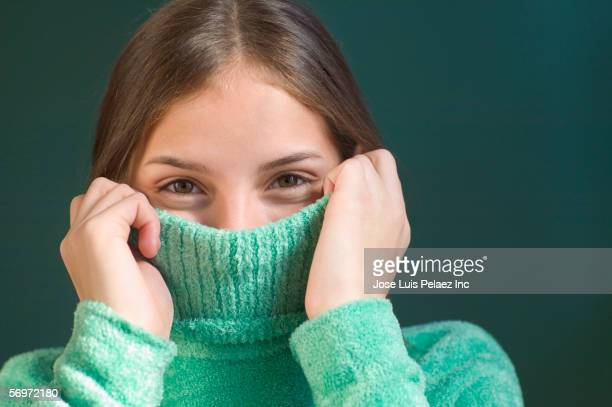 portrait of girl with turtleneck sweater over mouth - turtleneck stock pictures, royalty-free photos & images
