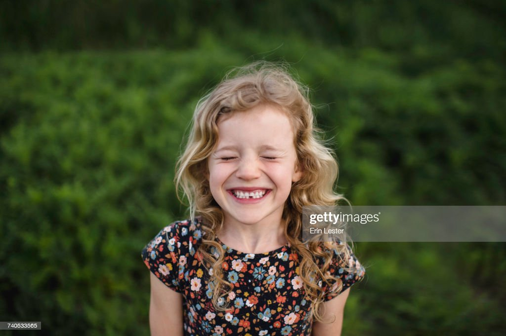 Portrait of girl with wavy blond hair and missing tooth in field : Stock-Foto