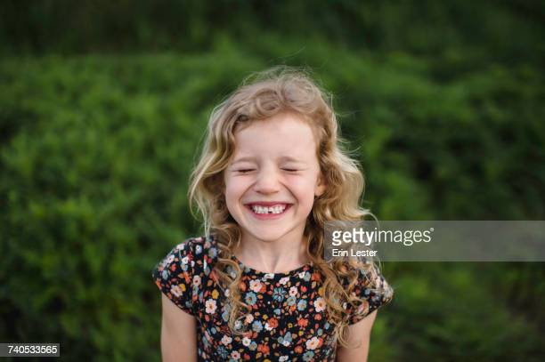 Portrait of girl with wavy blond hair and missing tooth in field