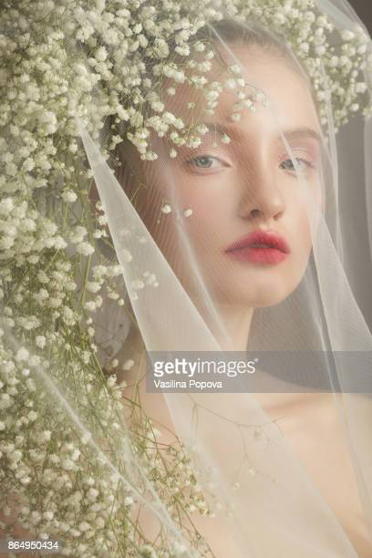 Portrait of girl with white flowers and veil