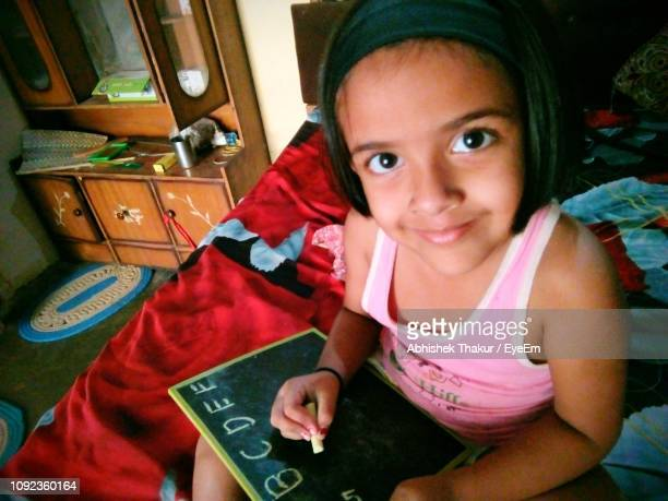 Portrait Of Girl Writing On Blackboard On Bed At Home