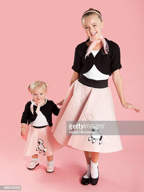 portrait of girls (12-17 months) and (10-11) in 1950s style costumes for halloween - poodle skirt stock photos and pictures