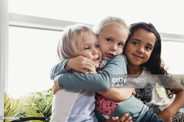 Portrait of girls embracing in day care center