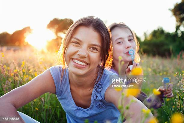 Portrait of girls sitting in field, one blowing bubbles
