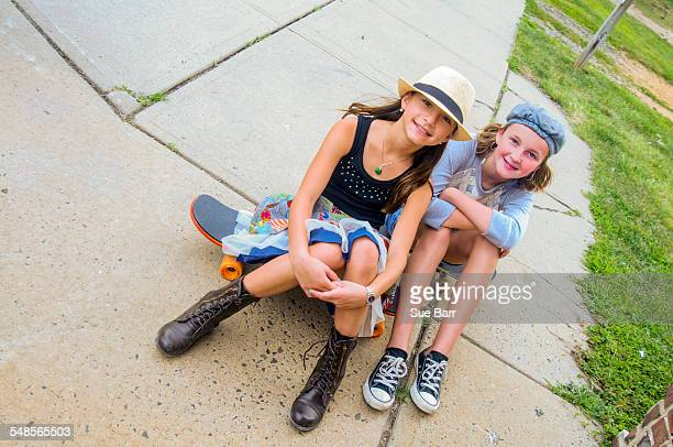 Portrait of girls sitting on skateboards