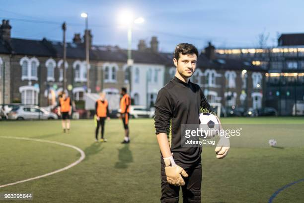portrait of goalkeeper with football under arm looking towards the camera on pitch at dusk - amateur stock pictures, royalty-free photos & images
