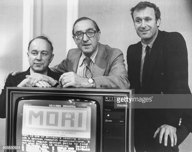 Portrait of 'Good Morning Television' broadcasters Ned Sherrin Peter Hardiman Scott and Julian Pettifer standing with a television set as Hardiman...