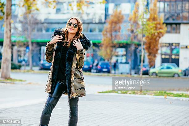 portrait of good-looking young woman in downtown in autumn - camouflage clothing stock pictures, royalty-free photos & images