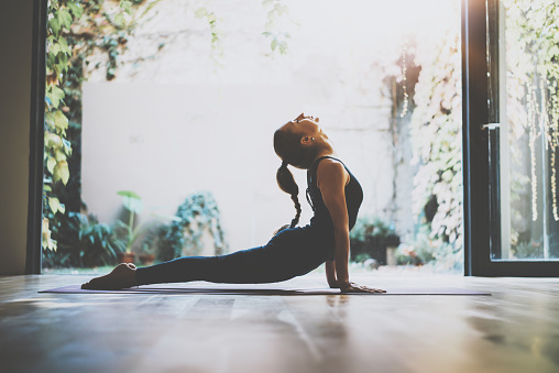 Portrait of gorgeous young woman practicing yoga indoor. Beautiful girl practice cobra asana in class.Calmness and relax, female happiness.Horizontal, blurred background.Visual effects. 815199586