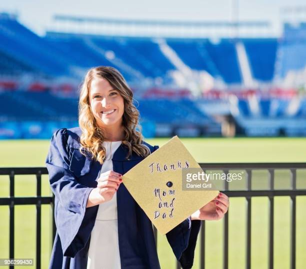 Portrait of graduate student showing message on mortarboard