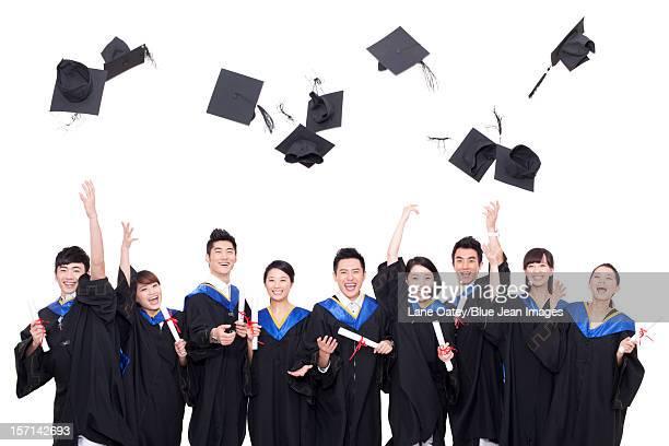 Portrait of graduates throwing mortar boards