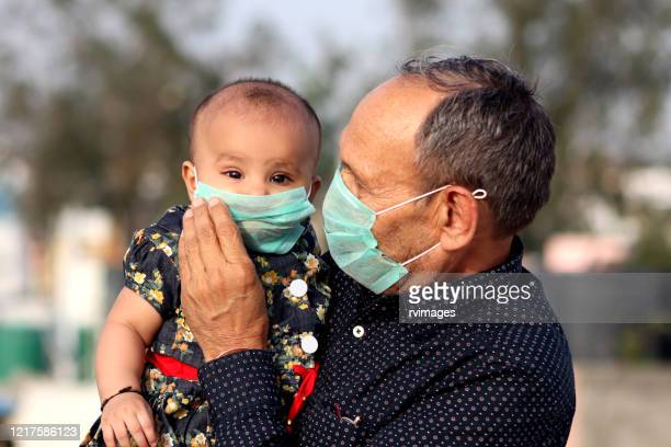 portrait of grandfather and grandchild with pollution mask against covid-19 - india stock pictures, royalty-free photos & images