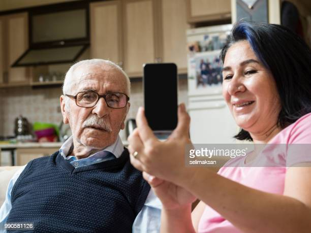 Portrait Of Grandfather And Granddaughter Looking At Mobile Phone