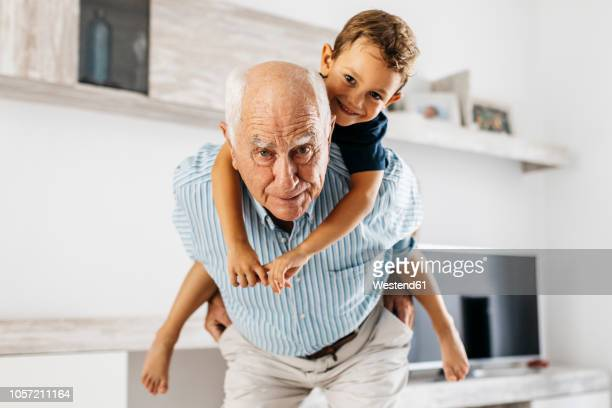 portrait of grandfather giving his grandson a piggyback ride in the living room - grandfather stock pictures, royalty-free photos & images
