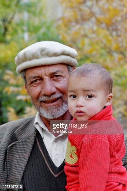 portrait of grandfather with his granddaughter and looking at camera. - skardu stock pictures, royalty-free photos & images