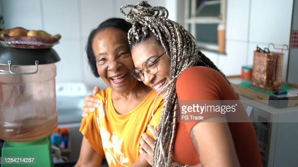 portrait of grandmother and granddaughter embracing at home - brazilian ethnicity stock pictures, royalty-free photos & images