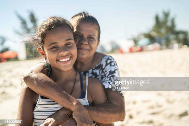 portrait of grandmother and granddaughter embracing in the beach - mixed race person stock pictures, royalty-free photos & images