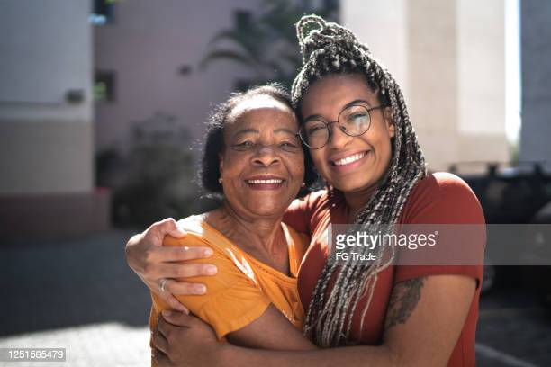 portrait of grandmother and granddaughter embracing outside - brazilian ethnicity stock pictures, royalty-free photos & images