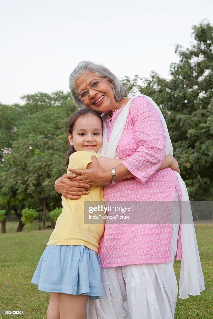 Portrait of grandmother and granddaughter hugging : Stock Photo