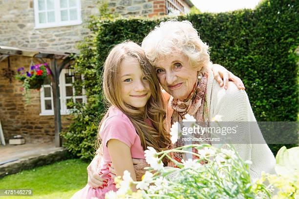 portrait of grandmother and granddaughter with arms around each other - british granny stock photos and pictures