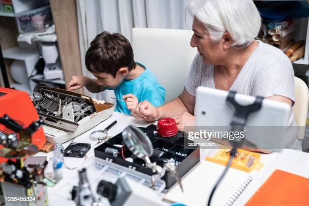 Portrait Of Grandmother And Grandson Repairing Typewriter