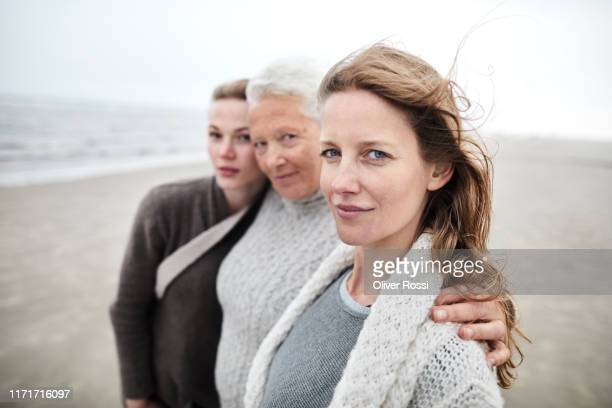 portrait of grandmother, mother and daughter on the beach - drei personen stock-fotos und bilder