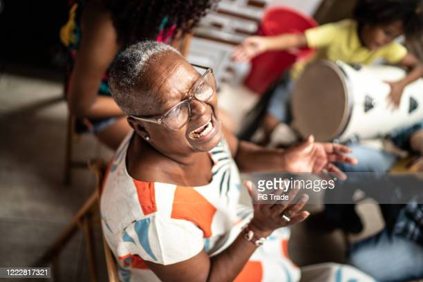 portrait of grandmother playing music at home - with family on background - samba stock pictures, royalty-free photos & images