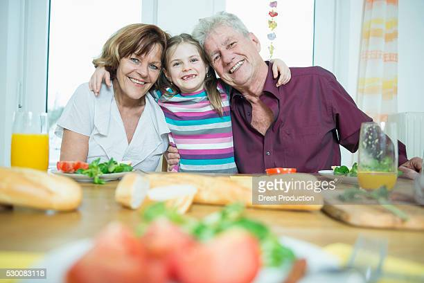 Portrait of grandparents and granddaughter having meal, smiling