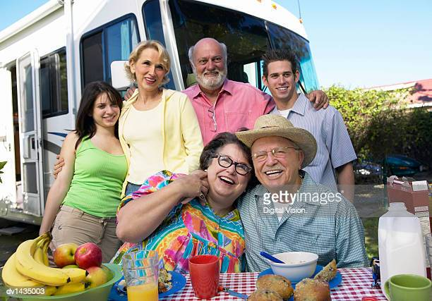 Portrait of Grandparents and Their Grandchildren Having an Outdoor Picnic in Front of Their Motor Home