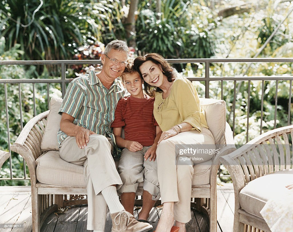Portrait of Grandparents Sitting With Their Grandson on a Sofa on a Balcony : Stock Photo