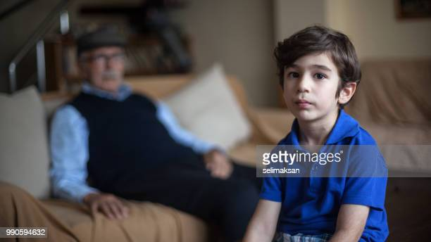 Portrait Of Grandson And Great Grandfather In Living Room