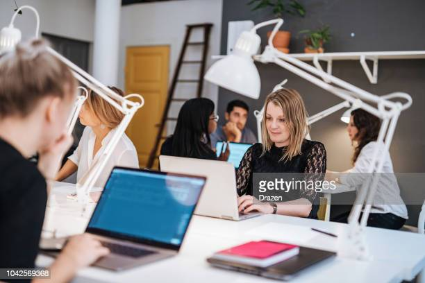 portrait of graphic designer in scandinavia, working on laptop. - hot desking stock pictures, royalty-free photos & images