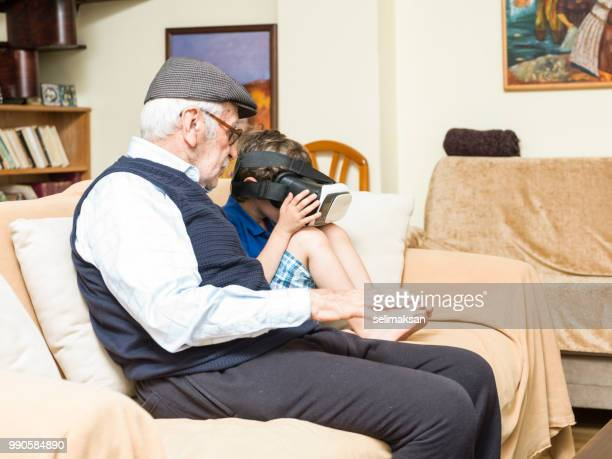 portrait of great grandfather and grandson sitting on sofa - horn rimmed glasses stock pictures, royalty-free photos & images