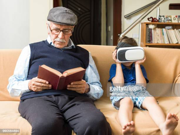 portrait of great grandfather and grandson sitting on sofa - storyteller stock pictures, royalty-free photos & images