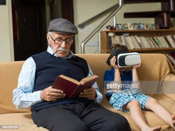 Portrait Of Great Grandfather And Grandson Sitting On Sofa