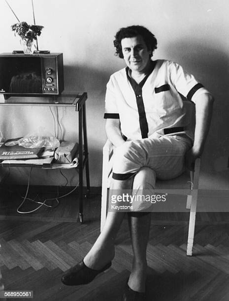 Portrait of Greek composer and musician Mikis Theodorakis sitting in an armchair next to a television circa 1968 Printed following his appendicitis...