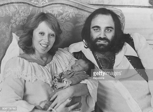 Portrait of Greek singer Demis Roussos sitting on a bed with wife and newborn baby September 18th 1975