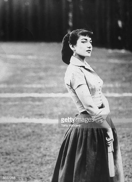 Portrait of GreekAmerican opera singer Maria Callas standing outdoors in a field and holding a hand fan Rome Italy