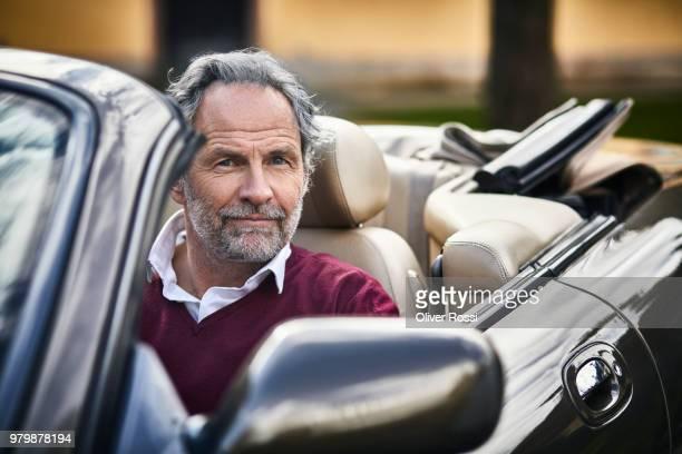 portrait of grey-haired man sitting in convertible car - prosperity stockfoto's en -beelden