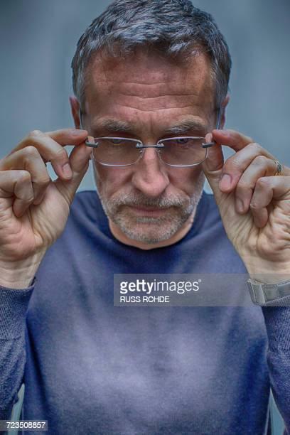 portrait of greying mature man removing glasses - strip - fotografias e filmes do acervo
