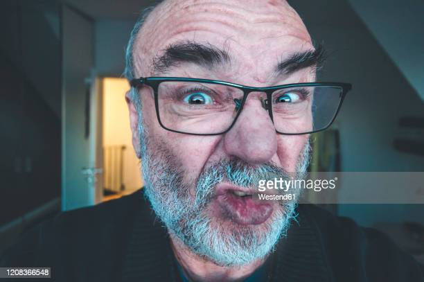 portrait of grimacing senior man - ugly bald man stock pictures, royalty-free photos & images